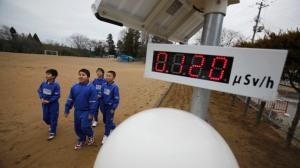 Les élèves marchent près d'un compteur Geiger, mesurer un niveau de 0,12 microsievert par heure de rayonnement, à Omika Elementary School, située à environ 21 km (13 miles) de la Fukushima Daiichi centrale nucléaire de tsunami-paralysé, dans Minamisoma, la préfecture de Fukushima.