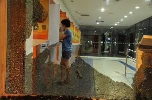 Une femme est vu à travers une vitre cassée à une succursale bancaire  (guichet automatique) après une protestation contre la Coupe du Monde de la FIFA, à Rio de Janeiro, près du stade Maracana, le 15 Juin 2014.