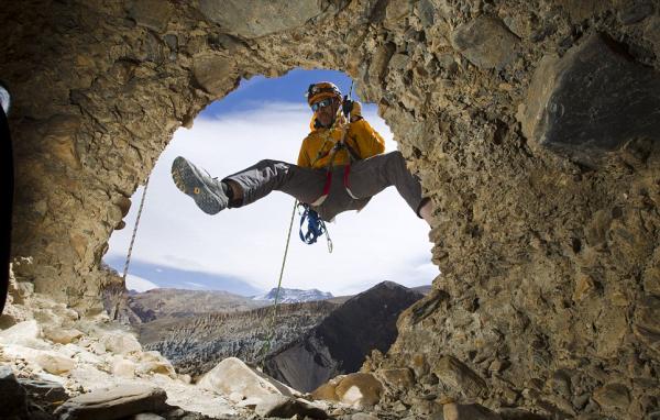 Grimpeur Pete Athans regarde à l'intérieur d'une grotte trouvée près Chuksang. On ne sait pas comment les gens montaient dans les grottes qui sont creusées dans une falaise au-dessus 155foot le fond de la vallée