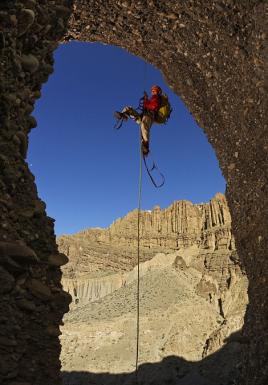 qu'un autre membre de l'équipe se hisse à une entrée d'une grotte Mustang,