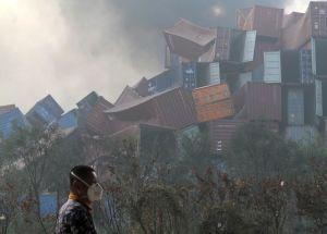 Face à une montagne de conteneurs soufflés par l'explosion,un homme portantun masque marche tranquillement.