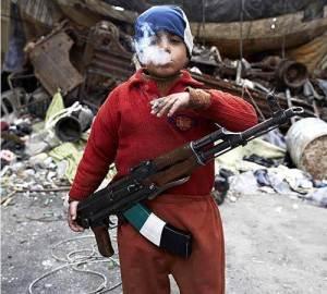 Un enfant-soldat âgé de seulement 7 ans ,fume une cigarette d'un air menaçant.Membre de la Syrian Free Army ,soutenue par les États-Unis d'Amérique,cet enfant a du subir un lavage de cerveau.