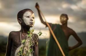 Garçon de la tribue nomade Suri de l'Éthiopie,avec ses peintures traditionnelles et son costume d'attraits.
