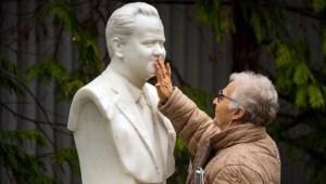 Une vieille militante vient se recueillir devant son buste.