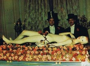 Cette photo fait nettement penser à la mise en scène d'un sacrifice avec une femme nue ayant une expression sur le visage exprimant la douleur et qui porte sa main à son cou qui semble avoir été blessé, le tout dans une mise en scène macabroc-chic des plus dérangeante.