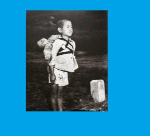 Cette photographie  de 1945 déchirante montre un jeune garçon debout à l'attention après avoir amené son frère mort à un site de crémation.Ceci se passait après l'explosion d'Hiroshima.